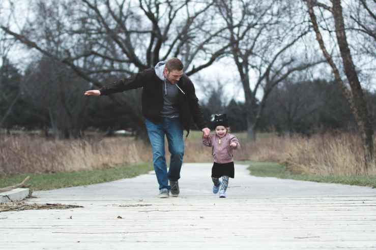 photo of father and daughter running at the park